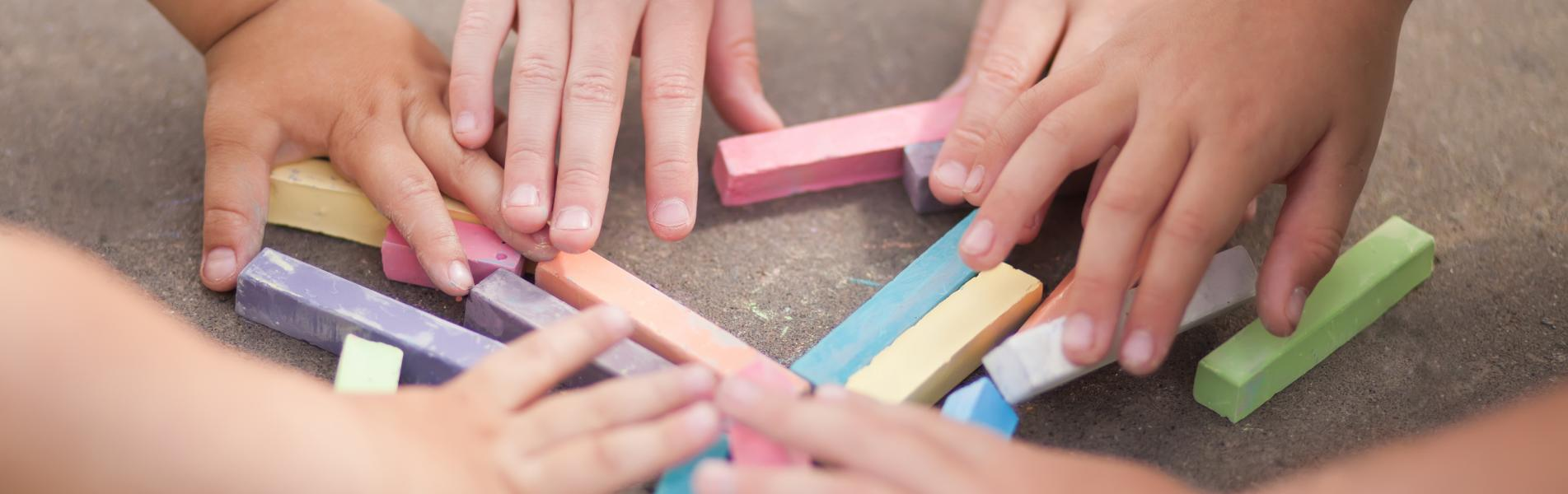 3 pairs of children's hands are touching a pile of coloured chalk on the ground