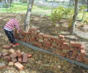 child building a brick wall