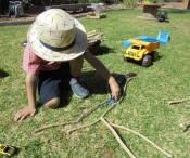 child building with sticks