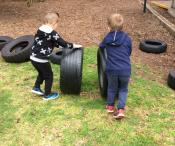 Two children are rolling tyres on grass