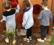 Three children are washing circular red pieces of glass in a wooden door with toothbrushes