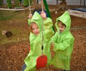 One girl is pushing another girl on the swing. Both girls are dressed in rain-jackets.