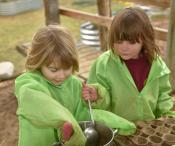 2 children mixing clay and mud together in a saucepan,  to make mud cakes