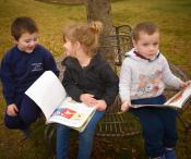 3 children sitting on a bench around a tree reading books to each other.
