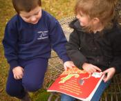 A girl and a boy sitting on a bench outside, sharing a book