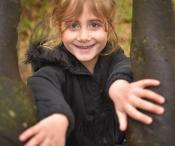A girl posing for a photo between to branches of a tree.
