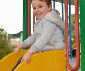 A boy at the top of a yellow slide.