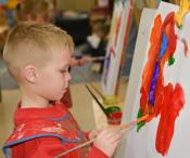 Young boy drawing a picture using paint.