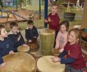 a group of children playing drums, using their hands to create a beat.