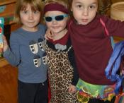 Three children playing dress up and posing for a photo.