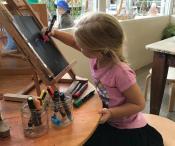 Child creating artwork on black card.