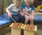 Two children are sitting outside playing short xylophones
