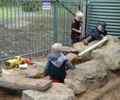 Three boys are playing on large rocks with a plastic pipe which has water running through it.