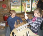 two children constructing a cardboard object