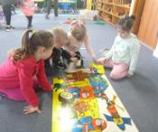 children looking at a poster on the floor